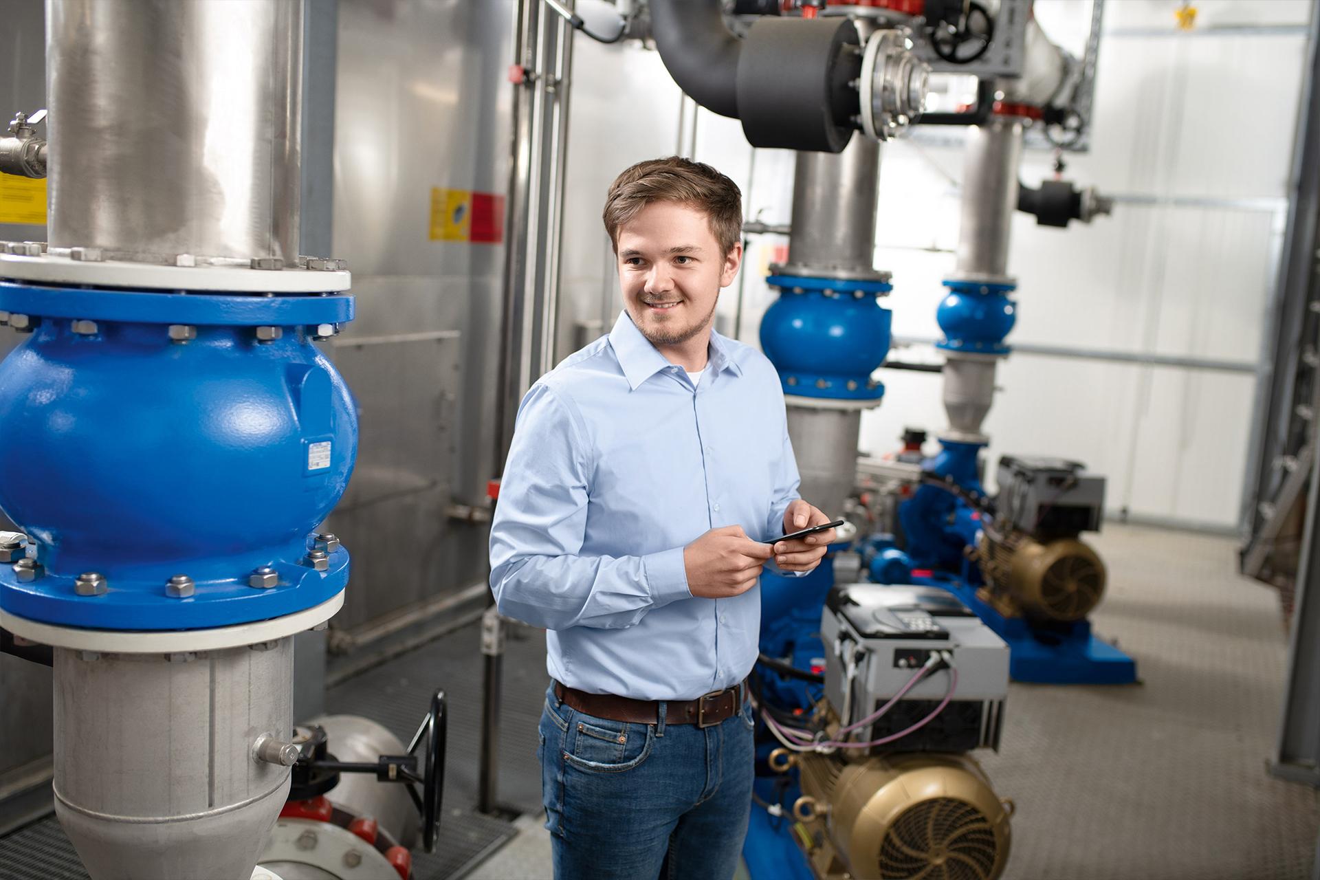 Ein Anlagenbetreiber steht mit einem Smartphone neben seinen Pumpen.
