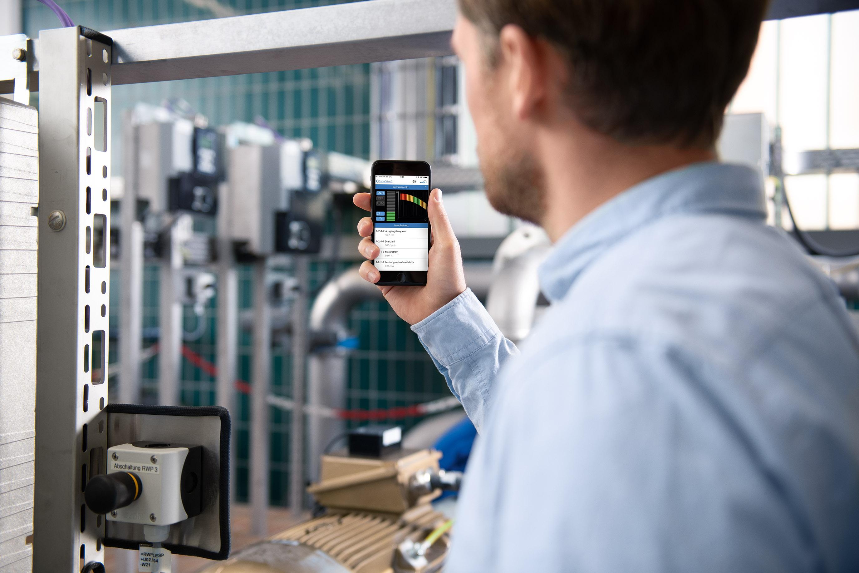 Ein Anlagenbetreiber steht mit seinem Smartphone inmitten seiner Anlage.