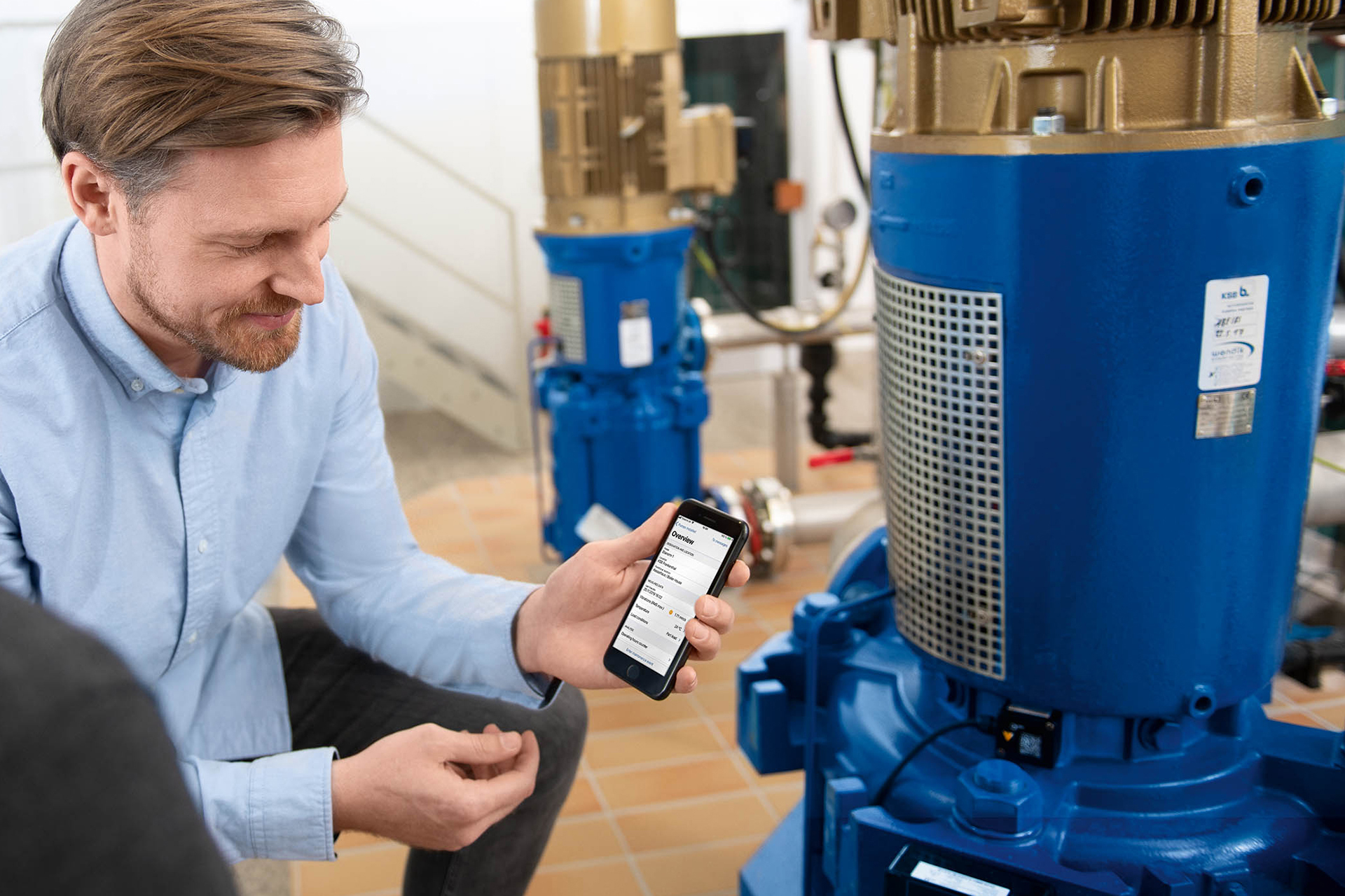 A system operator with a smartphone standing next to a pump equipped with KSB Guard