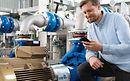 Ein Anlagenbetreiber mit einem Smartphone steht neben einer mit KSB Guard ausgestatteten Pumpe.